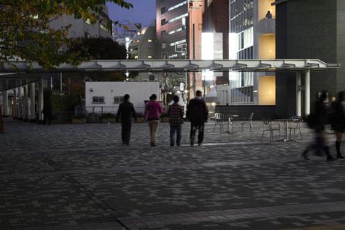 日の落ちた新宿の街をオフィスへ戻るメンバー